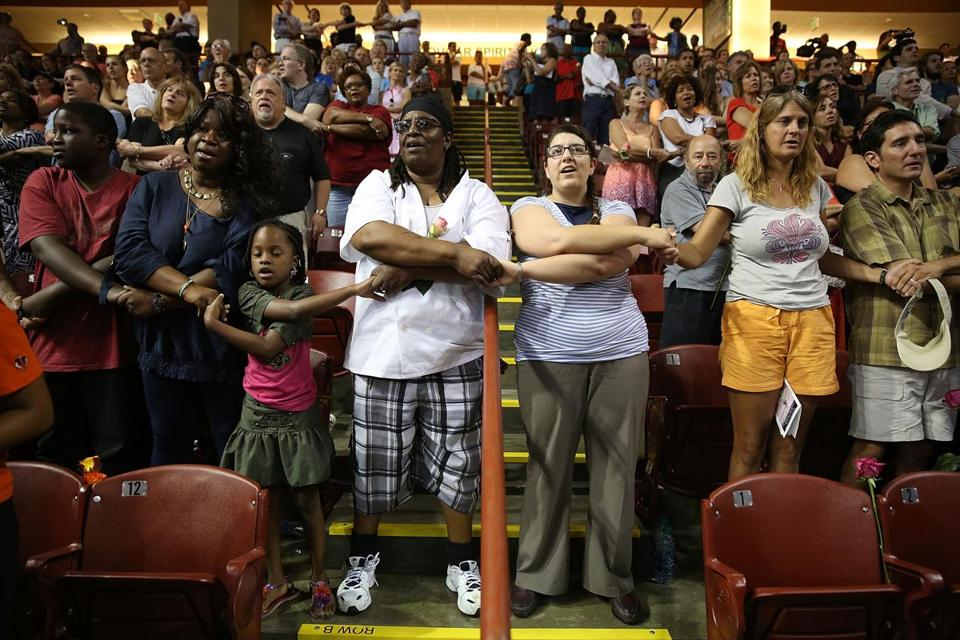 CHARLESTON, SC - JUNE 19: People join hands during a prayer vigil at the TD Arena on June 19, 2015 in Charleston, South Carolina. The vigil is held in honor of those lost during a mass shooting at the Emanuel African Methodist Episcopal Church, one of the nation's oldest black churches, when Dylann Roof, 21, reportedly shot nine people during a prayer meeting. (Photo by Joe Raedle/Getty Images)
